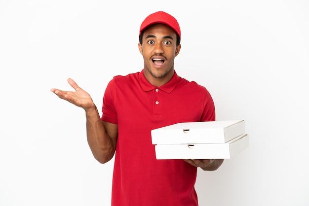 Афро-американский доставщик пиццы собирает коробки для пиццы над изолированной белой стеной с шокированным выражением лица