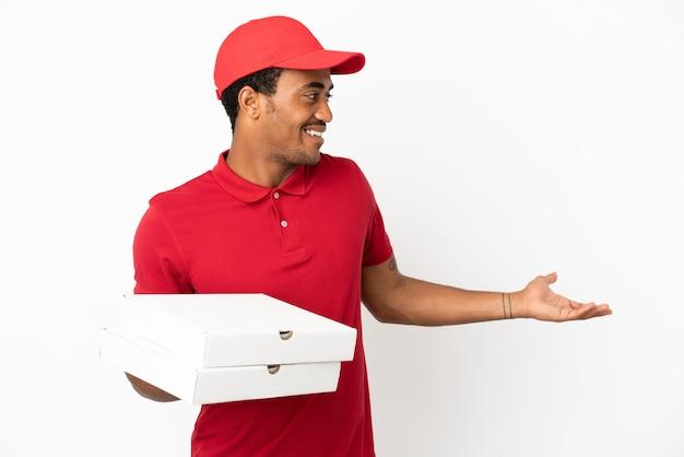 アフリカ系アメリカ人のピザ配達人が側面を見ながら驚きの表情で孤立した白い壁の上のピザの箱を拾う