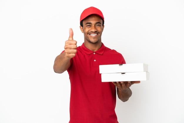 何か良いことが起こったので、親指を立てて孤立した白い壁の上のピザの箱を拾うアフリカ系アメリカ人のピザ配達人