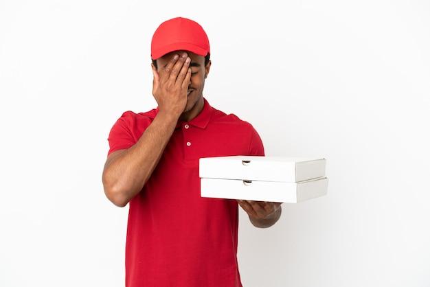 Афро-американский доставщик пиццы собирает коробки для пиццы над изолированной белой стеной с усталым и больным выражением лица