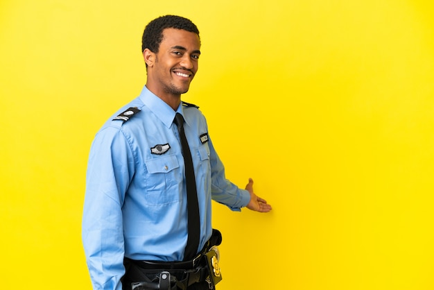 African american police man over isolated yellow background extending hands to the side for inviting to come