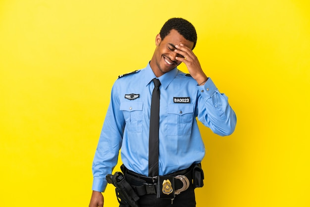 African american police man over isolated yellow background laughing