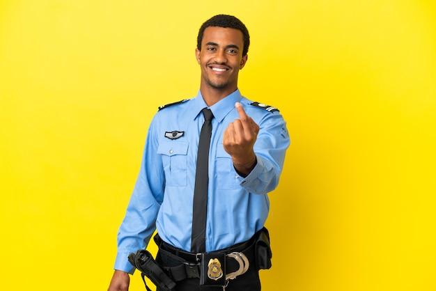 Афро-американский полицейский на изолированном желтом фоне делает приближающийся жест