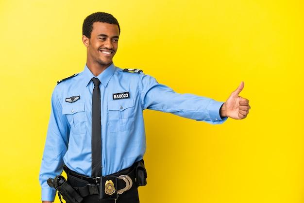 親指を立てるジェスチャーを与える孤立した黄色の背景上のアフリカ系アメリカ人の警官
