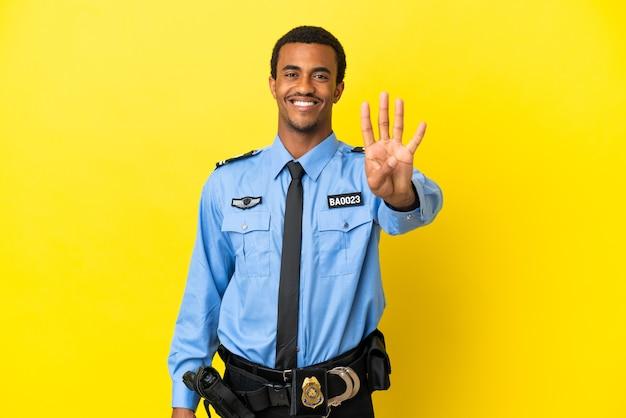 Афро-американский полицейский на изолированном желтом фоне счастлив и считает четыре пальцами