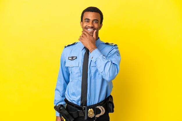 Афро-американский полицейский на изолированном желтом фоне счастливы и улыбаются