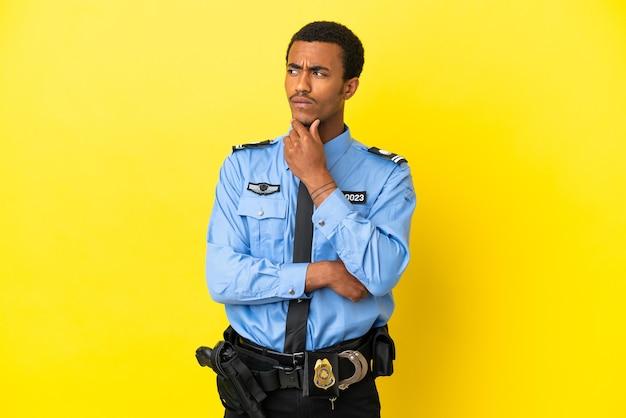 Афро-американский полицейский на изолированном желтом фоне с сомнениями и мышлением