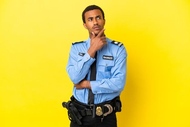 격리된 노란색 배경 위에 있는 아프리카계 미국인 경찰은 찾는 동안 의심을 품고 있습니다.