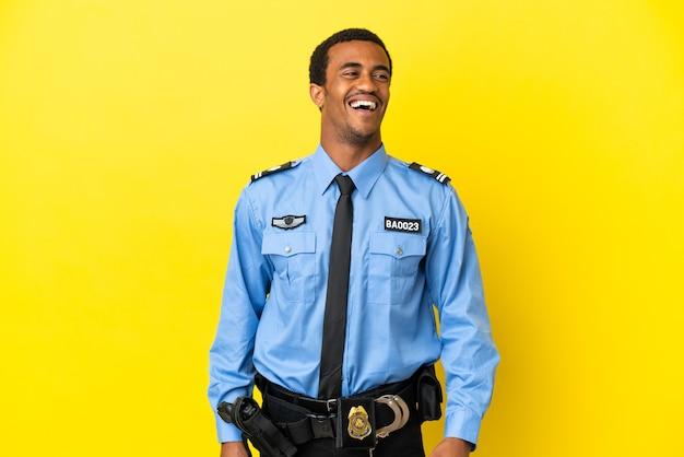 고립 된 노란색 배경 웃 고 위에 아프리카 계 미국인 경찰 남자