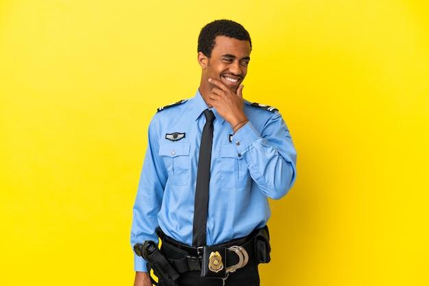 외진 노란색 배경 위에 있는 아프리카계 미국인 경찰은 옆을 바라보며 웃고 있다