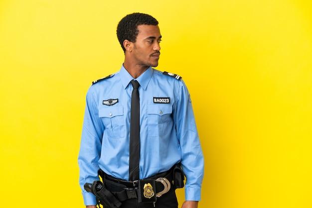 Афро-американский полицейский на изолированном желтом фоне, глядя в сторону