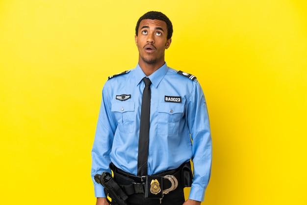 Афро-американский полицейский на изолированном желтом фоне смотрит вверх и с удивленным выражением лица