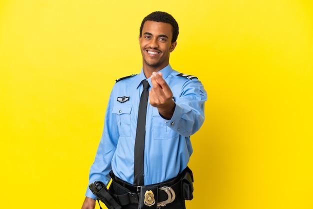 Афро-американский полицейский на изолированном желтом фоне делает денежный жест