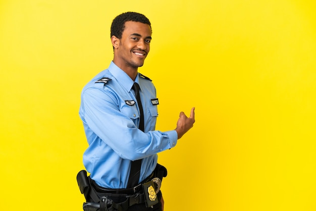 뒤로 가리키는 고립 된 노란색 배경 위에 아프리카 계 미국인 경찰 남자