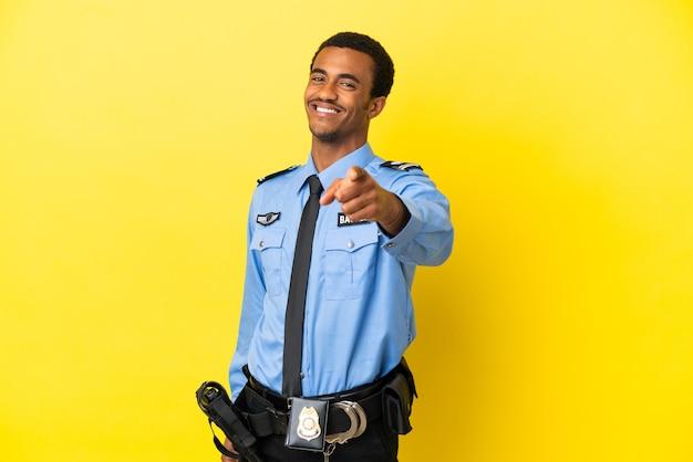Афро-американский полицейский над изолированным желтым фоном, указывая вперед с счастливым выражением лица