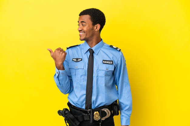 제품을 제시하기 위해 측면을 가리키는 고립 된 노란색 배경 위에 아프리카 계 미국인 경찰 남자