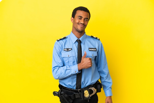 Афро-американский полицейский на изолированном желтом фоне гордый и самодовольный