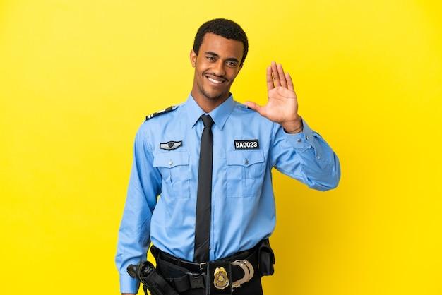 Афро-американский полицейский на изолированном желтом фоне, салютуя рукой с счастливым выражением лица