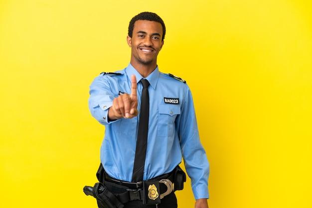 Афро-американский полицейский на изолированном желтом фоне показывает и поднимает палец