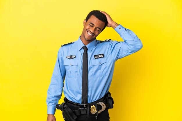 Афро-американский полицейский на изолированном желтом фоне много улыбается