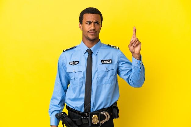 Афро-американский полицейский на изолированном желтом фоне со скрещенными пальцами и желанием всего наилучшего