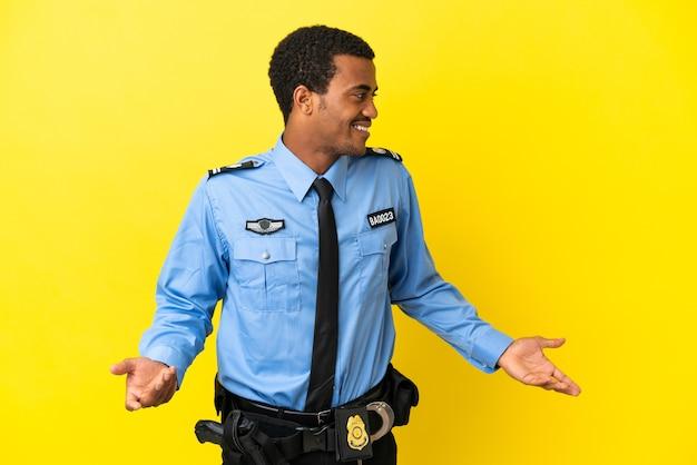 Афро-американский полицейский на изолированном желтом фоне с удивленным выражением лица, глядя в сторону