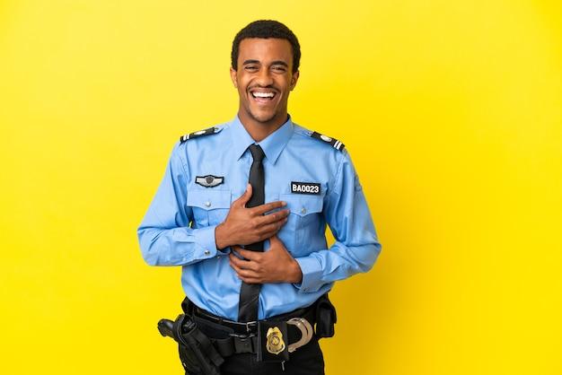 많이 웃 고 고립 된 노란색 표면에 아프리카 계 미국인 경찰 남자