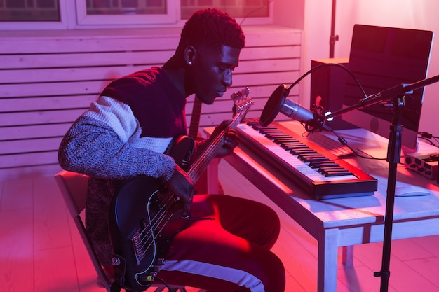 African american professional musician recording guitar in digital studio at home, music production