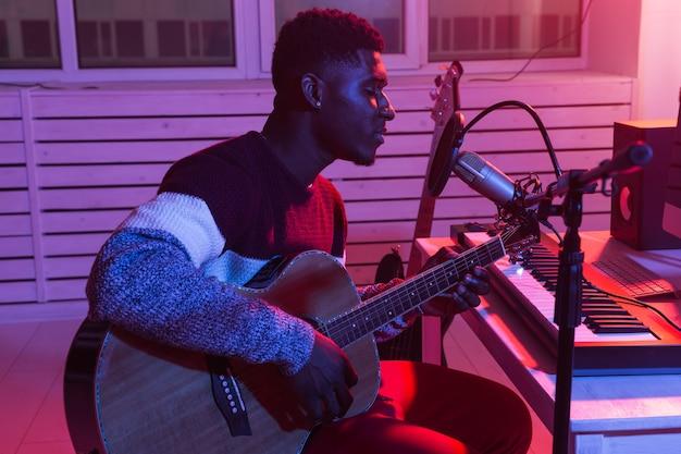 Афро-американский профессиональный музыкант, записывающий гитару в цифровой студии дома, концепция технологии производства музыки, крупный план.