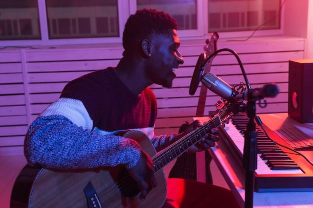 アフリカ系アメリカ人のプロのミュージシャンが自宅のデジタルスタジオでギターを録音、音楽制作