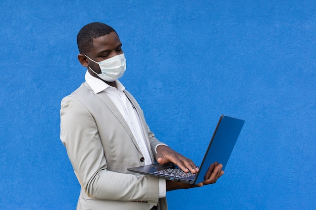 African american in a protective mask with a laptop in his hand
