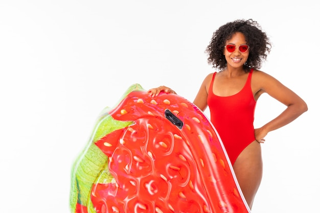 African american in a red bathing suit on a white  with a mattress for the pool in her hands