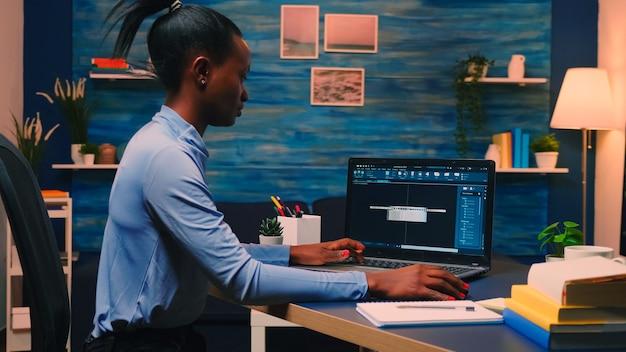 現代のcadプログラムの残業に取り組んでいるアフリカ系アメリカ人のリモート女性建築家。デバイスのディスプレイにソフトウェアを表示するパソコンでプロトタイプのアイデアを研究している産業黒人女性エンジニア