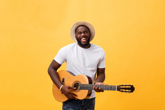 African american retro styled guitarist playing acoustic guitar isolated on yellow background.