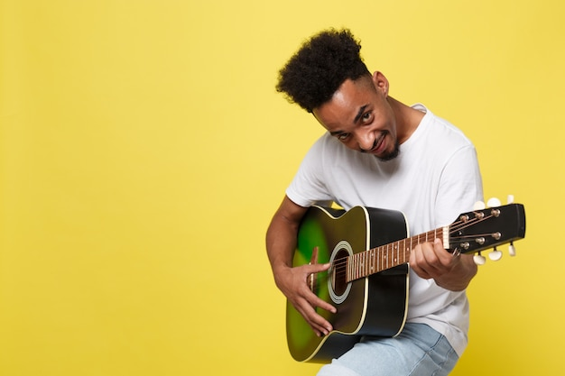 African american retro styled guitarist playing acoustic guitar