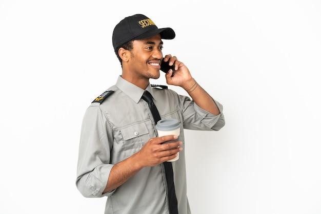 Афро-американская охрана на изолированном белом фоне держит кофе на вынос и мобильный