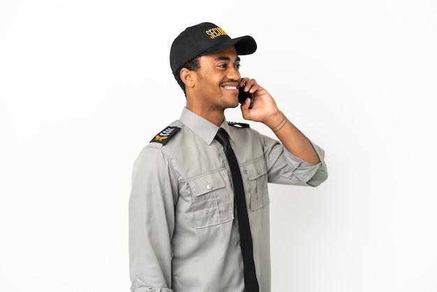 Афро-американская охрана на изолированном белом фоне, разговаривая по мобильному телефону