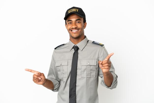 Афро-американская охрана на изолированном белом фоне, указывая пальцем на боковые стороны и счастливым