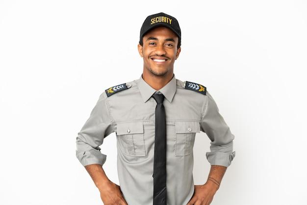 Афро-американская охрана на изолированном белом фоне позирует с руками на бедрах и улыбается