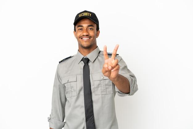 Афро-американская охрана на изолированном белом фоне улыбается и показывает знак победы