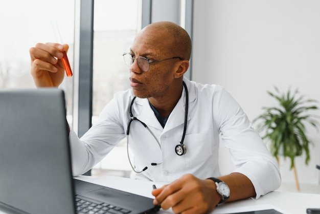 試薬で試験管を保持し、検査する白衣のアフリカ系アメリカ人の科学者