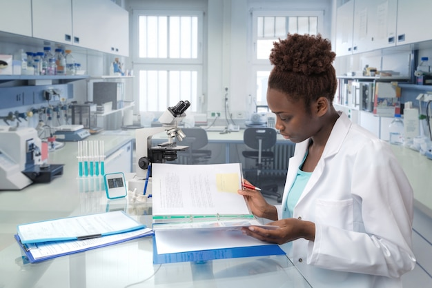 African-american scientist reading laboratory journal in research facility