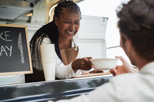 African american senior woman serving take away food inside food truck - focus on female face
