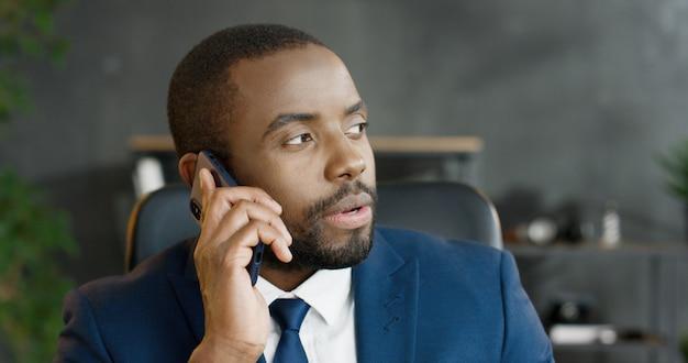 アフリカ系アメリカ人の真面目なサラリーマンがスマートフォンで話しています。携帯電話での会話を持つ男性。