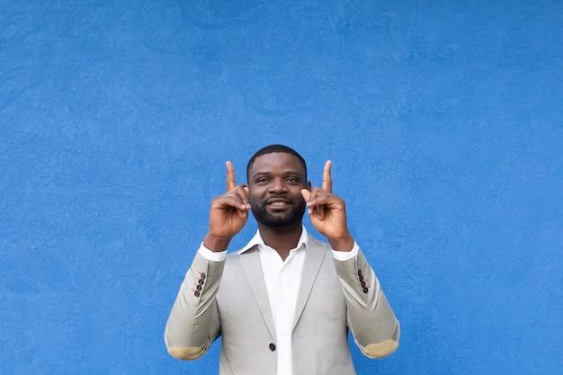 아프리카 계 미국인은 파란색 배경에 손을 보여줍니다.