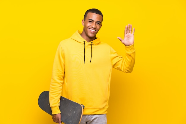 African american skater man saluting with hand with happy expression