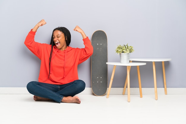 African american skater teenager girl with braided hair sitting on the floor celebrating a victory