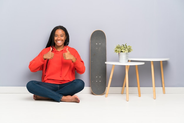 African american skater teenager girl with braided hair sitting on the floor giving a thumbs up gesture