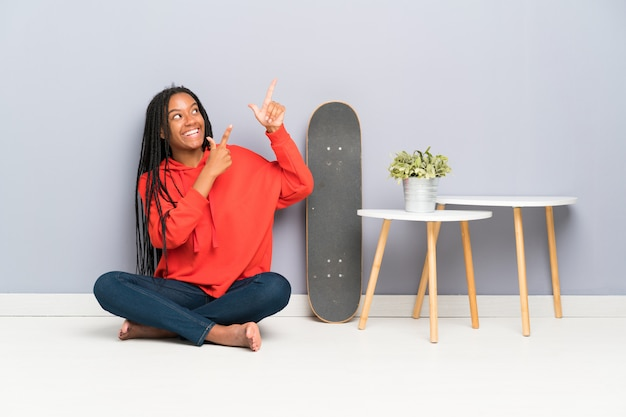 African american skater teenager girl with braided hair sitting on the floor pointing with the index finger a great idea