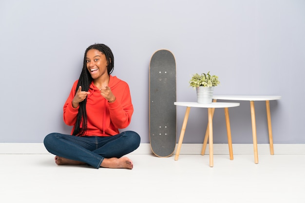 African american skater teenager girl with braided hair sitting on the floor points finger at you